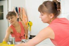 Le femme lave un miroir Photographie stock libre de droits