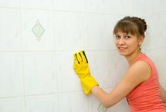 Le femme lave une tuile Photos stock