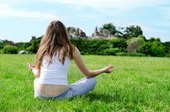Le femme médite sur la pelouse verte photo libre de droits