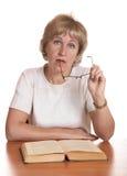 Le femme mûr avec le livre derrière une table Images stock