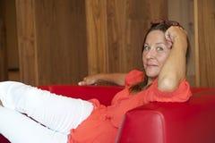 Le femme mûr a détendu sur le divan Image stock