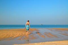 Le femme marche sur la plage Image stock