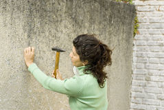 Le femme martèle le clou dans le mur - horizontal photos libres de droits