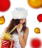 Le femme mignon ouvrent le cadeau de Noël Image libre de droits