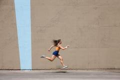 Le femme musculaire sprints pour gagner photos libres de droits