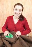 Le femme nettoyant une basane avec battent le balai image stock