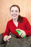 Le femme nettoyant une basane avec battent le balai photos stock