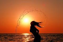 Le femme ont un amusement en mer au coucher du soleil Photo stock