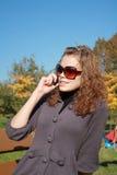 Le femme parle par le téléphone l'après-midi Images stock