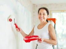 Le femme peint le mur avec le rouleau Photographie stock libre de droits
