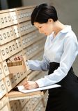 Le femme recherche quelque chose dans le catalogue de carte Image libre de droits
