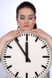 Le femme regarde sur l'horloge Image stock