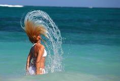Le femme renverse le cheveu dans les eaux de turquoise photographie stock libre de droits