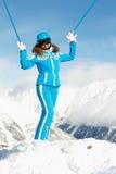 Le femme reste se levant vers le haut de ses mains avec le ski Image libre de droits