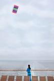 Le femme reste sur le paquet de doublure de vitesse normale et pilote le cerf-volant Images libres de droits
