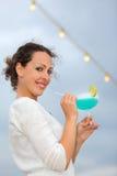Le femme reste sur le paquet de doublure et retient le cocktail Photographie stock