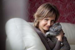 Le femme s'asseyant sur le divan et caresse le chat gris Photo libre de droits