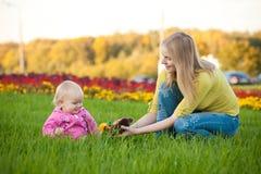 Le femme s'asseyent sur l'herbe verte près des bâtis des fleurs image stock