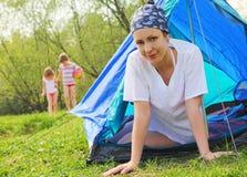Le femme s'assied à l'intérieur de la tente, jeu de gosses sur la pelouse Photographie stock libre de droits