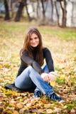 Le femme s'assied sur des lames en automne Image libre de droits
