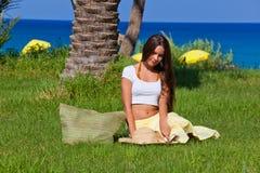 Le femme s'assied sur l'herbe verte près de la mer Photographie stock libre de droits