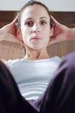 Le femme s'exerçant et s'asseyent se lève Image libre de droits