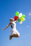 Le femme sautant avec des ballons image stock