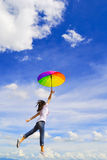 Le femme sautant avec le ciel bleu Photographie stock libre de droits