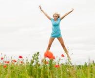 Le femme sautant dans un domaine de pavot Photographie stock libre de droits