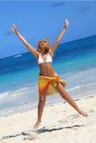 Le femme sautant sur la plage image stock