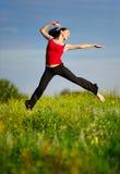 Le femme sautant sur un coucher du soleil Photos stock