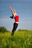 Le femme sautant sur un coucher du soleil Photographie stock libre de droits
