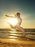 Le femme sautant sur une plage Photos stock