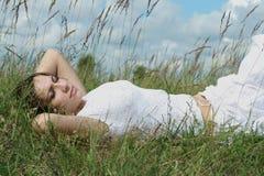 Le femme se trouve sur l'herbe Photo libre de droits