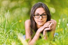 Le femme se trouve sur l'herbe verte Photographie stock