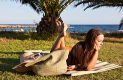 Le femme se trouve sur l'herbe verte près de la mer Photos stock