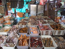 Le femme thaï vend les poissons secs sur un marché, Thaïlande. Images stock