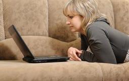 Le femme travaillant sur l'ordinateur portatif à la maison photographie stock