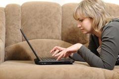 Le femme travaillant sur l'ordinateur portatif à la maison photo stock