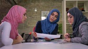 Le femmine arabe sicure del hijab stanno lavorando insieme al desktop, stanno sedendo e parlando a vicenda, dell'interno stock footage