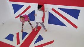 Le femmine graziose a colori vestiti allegro stanno ballando sulla bandiera BRITANNICA del fondo stock footage