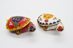 Le feng-shui deux a coloré des tortues en métal avec la coquille détachable de carapace pour des bijoux déposant sur le fond blan images stock