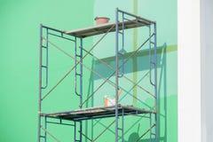 Le fer d'échafaudage avec le mur vert et la peinture bucket Photos stock