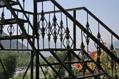 Le fer travaillé fait un pas dans la maison de montagne avec une vue Photographie stock libre de droits