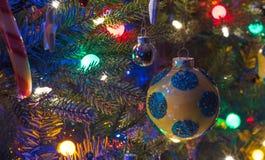 Le ferie, decorazioni dell'albero di Natale emettono luce nell'ambito delle luci luminose e vive, variopinte su un albero dell'in Immagini Stock Libere da Diritti