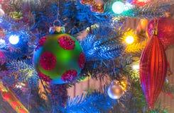 Le ferie, decorazioni dell'albero di Natale emettono luce nell'ambito delle luci luminose e vive, variopinte su un albero dell'in Fotografia Stock Libera da Diritti