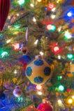Le ferie, decorazioni dell'albero di Natale emettono luce nell'ambito delle luci luminose e vive, variopinte su un albero dell'in Fotografie Stock