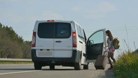 Le fermate dell'automobile vicino all'autostoppista della ragazza stock footage