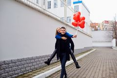 Le ferroutage de fille sur le type avec le coeur rouge monte en ballon sur la rue Photos libres de droits