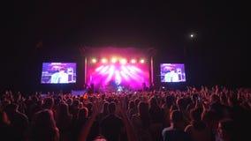 Le festival de roche, beaucoup de fans battent et ondulent des mains au concert de musique en direct contre l'étape brillamment a banque de vidéos